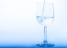Drinking water is poured from a bottle into a glass Royalty Free Stock Photography