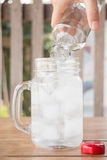 Drinking water is poured into iced glass Royalty Free Stock Images