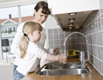 Drinking water. Small Girl in the kitchen with her mother drinking water Stock Photography