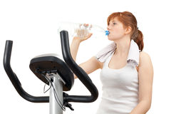 Drinking water woman on training bicycle Stock Photos