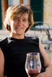 Drinking wine. Woman with a glass of wine sitting outside in the sun royalty free stock photography