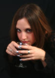 Drinking Wine. Young female drinking from glass goblet Royalty Free Stock Photo