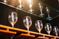 Drinking wine glasses shelf in restaurant with lighting showcase. Background. Many clean containers in restaurant or night pub and bar. Interior decoration and stock photo