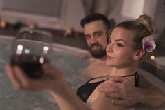 Drinking wine in a jacuzzi bath. Couple in love enjoying the romantic atmosphere of a jacuzzi bath, drinking wine and relaxing. Romantic wellness spa getaway Royalty Free Stock Images