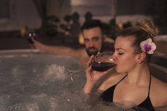 Drinking wine in a jacuzzi bath tub. Couple in love enjoying the romantic atmosphere of a jacuzzi bath, drinking wine and relaxing Royalty Free Stock Photography