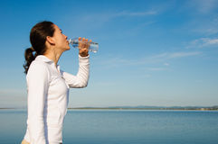 Drinking Woman. With a blue sky outside royalty free stock image