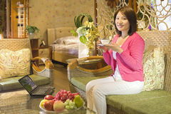 A drinking woman at home Royalty Free Stock Image