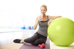 Drinking woman. Portrait of blonde fit woman driniking a bottle of water while standing at yoga mat after fintess workout at gym Royalty Free Stock Photos