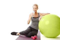 Drinking woman. Portrait of blonde fit woman driniking a bottle of water while standing at yoga mat after fintess workout. Isolated on white background Royalty Free Stock Photos