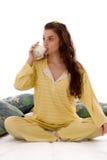 Drinking yogurt. Beautiful girl in pajamas drinking yogurt Royalty Free Stock Photo