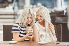 Drinkkaffe för två flickor och använder telefonen Royaltyfri Fotografi