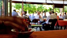 Drinkking turkish tea. The glass of hot tea ion a table in old fashioned tea house with numerous local senior gentlemen, enjoying their rest on open air terrace stock video