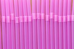 Drinkröret av rosa färger färgar i abstrakt bakgrund Arkivfoto