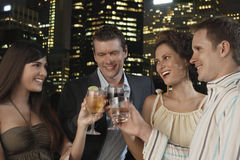 Drinks Against City Skyline At Night. Two young couples toasting drinks against city skyline at night Stock Images