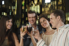 Drinks Against City Skyline At Night. Two young couples toasting drinks against city skyline at night Stock Photos