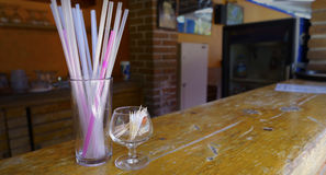 Drinks bar. An old wood bar in a drink area whit some straws in a glass and toothpicks in a little cup royalty free stock images