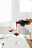 Drinks. Closeup Of Pouring Red Wine From Bottle Into Glass. Stock Image