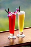 Drinks. Exotic Cocktails In Tropical Bar. Thailand Vacations. Ce. Drinks. Close Up Of Exotic Cocktails In Tall Glasses With Orchids And Drinking Straws On Wooden Royalty Free Stock Photo