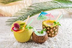 Drinks in fruits with cocktail umbrellas. On white pebbles stock image