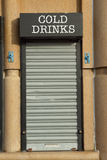 Drinks hatch. A sign with COLD DRINKS above a metal closed roller shutter Stock Image