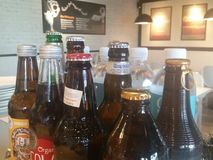 Drinks on the house. Bottles of beer from various brewery on display Royalty Free Stock Photos