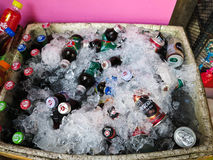 Drinks, many of which are immersed in a foam box being covered by ices for sale in the market. Stock Photo