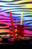 Drinks and Nibbles. 2 drinks with straws and selection of nibbles against a multicolored background royalty free stock images