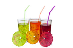 Drinks and Parasols. Three Glasses of refreshing iced drinks, with straws and Parasols. Isolated on white Royalty Free Stock Photos