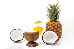 Drinks - Pina Colada. Pina colada in a coconut cup, garnished with umbrella and pineapple, and fresh ingredients, on a white background stock image