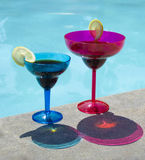 Drinks by the pool. Two drinks in colour coctail glass by the swimming pool Royalty Free Stock Images