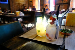 Drinks in a pub, low light. Good quality picture of stylish homemade style soft drinks: cute and quite stylish glass bottles, double drink pipes, a few berries Royalty Free Stock Images