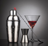 Drinks shaker with cocktail tools and glass. Cocktail tools with shaker, spoon and a glass filled with red liquid, square composition Royalty Free Stock Image