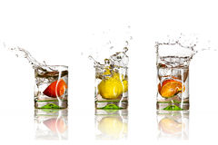 Drinks with splashing citrus fruits. Over white Royalty Free Stock Photo