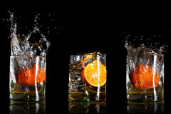 Drinks with splashing oranges Royalty Free Stock Images