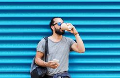 Man with smartphone drinking coffee over wall Royalty Free Stock Photo