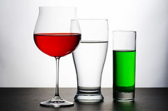 Drinks. A wine glassGrand Cru glass on a wooden table in front of a white background. Filled with a red wine Stock Images