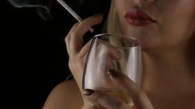 Drinkt de close-up blonde vrouw champagne en rook alleen in dark eenzame luxueus met een glas wijn Langzame Motie stock videobeelden