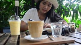 Drinkt de reizigers Thaise vrouw koffie na het schrijven van nota over het boek stock video