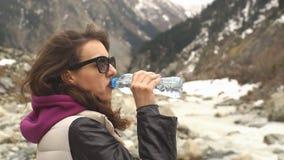 Drinkvatten för ung kvinna på en bakgrund av berg arkivfilmer