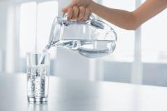 Drinkvatten Kvinnas hällande vatten för hand från kannan in i en Glas Arkivbild