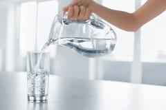 Drinkvatten Kvinnas hällande vatten för hand från kannan in i en Glas Royaltyfri Bild