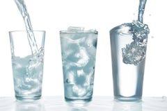 Drinkwater die in glas met ijsblokjes worden gegoten Stock Foto's