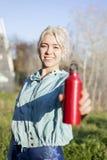Drinkwaterconcept Vrouwelijke agent die een rode fles houden stock fotografie