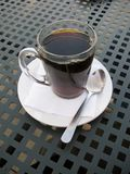Drip brewed coffee in clear glass mug. On patio table Royalty Free Stock Image