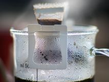 Pour-over and drip bag brewing coffee on cup. Drip brewing coffee. Ground coffee beans contained in a filter pour-over which involves pouring water with smoke royalty free stock photos