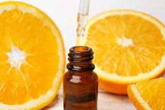 Dripping citrus essential oil into bottle. Closeup stock photo