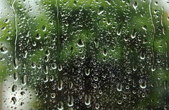 Dripping down drops of rain on glass Royalty Free Stock Photos