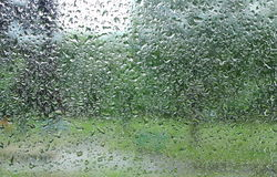 Dripping down drops of rain on glass Royalty Free Stock Photography