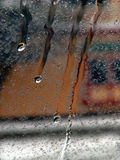 Dripping down window. Shows four streams of water dripping down window, leaving the background blurred and abstract Stock Photo