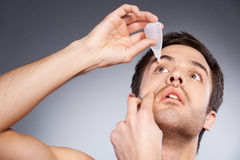Dripping eye with eye drops. Stock Image